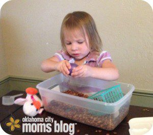 My youngest daughter playing with a sensory bin while I teach her older how to play chess.