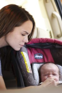 Mom giving baby a paci in the car