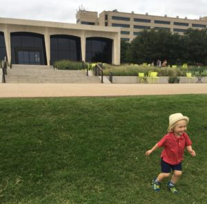Image of a young boy running down a small hill in front of the Amon Carter Museum in Fort Worth Texas.