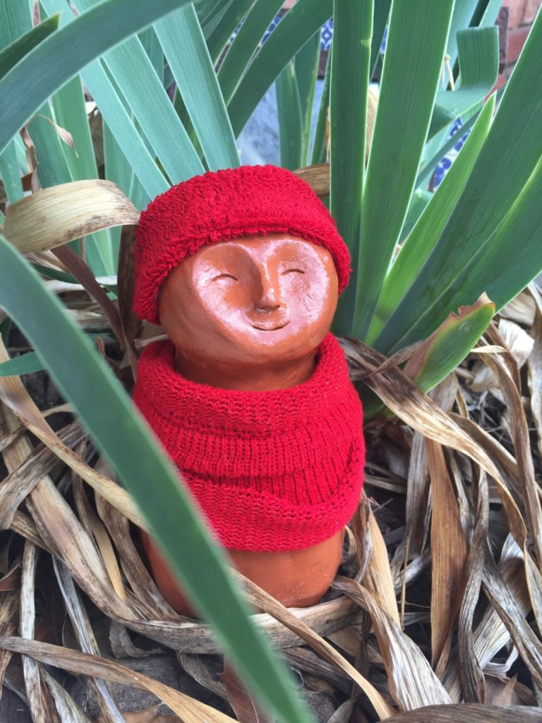 A 8 inch tall ceramic sculpture of a man wearing a red hat and red sweater is surrounded by plants.